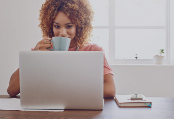 A woman sips from her coffee mug as she looks at her laptop.